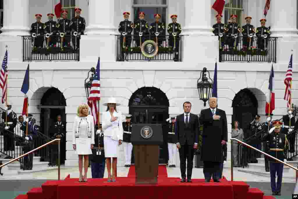 Le président Donald Trump et la première Dame Melania Trump avec le président français Emmanuel Macron et son épouse Brigitte Macron lors de la cérémonie d'arrivée sur la pelouse de la Maison Blanche à Washington, le 24 avril 2018