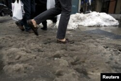 People cross slush and snow covered street in lower Manhattan in New York, Jan. 25, 2016.