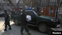 Afghan policemen stand guard at site where US advisor was killed by Afghan policewoman in Kabul, December 24, 2012