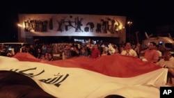 ຊາວອີຣັກ ພາກັນສະຫລອງ ດ້ວຍການຖືທຸງຊາດໃຫຍ່ ຢູ່ທີ່ຈະຕຸລັດ Tahrir ໃນນະຄອນ Baghdad ປະເທດ Iraq ວັນທີ 10 ກໍລະກົດ 2017.