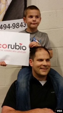 "Mark Jones of Summerville, whose son Rig is perched on his shoulders, holds a Marco Rubio sign at a South Carolina rally Feb. 19, 2016. Even after the rally, Jones says he's still undecided, though ""90 percent"" for Rubio. (C. Guensburg/VOA)"
