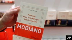 A man holds a book by French author Patrick Modiano at a book fair in Frankfurt, Germany, Oct. 9, 2014.