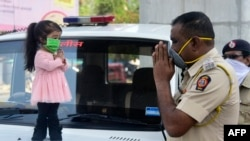 Guinness world record holder of the world's smallest living woman, Jyoti Amge (L), greets a police officer as she appeals citizens to stay inside their homes during a government-imposed nationwide lockdown as a preventive measure against the COVID-19 coro