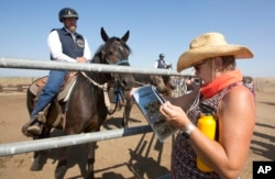 FILE - Prospective buyer Kimela Hancock looks over the program at the auction held by Wild Horse Program at the Sacramento County Sheriff's Department, Rio Cosumnes Correctional Center in Elk Grove, California, Sept. 10, 2016.