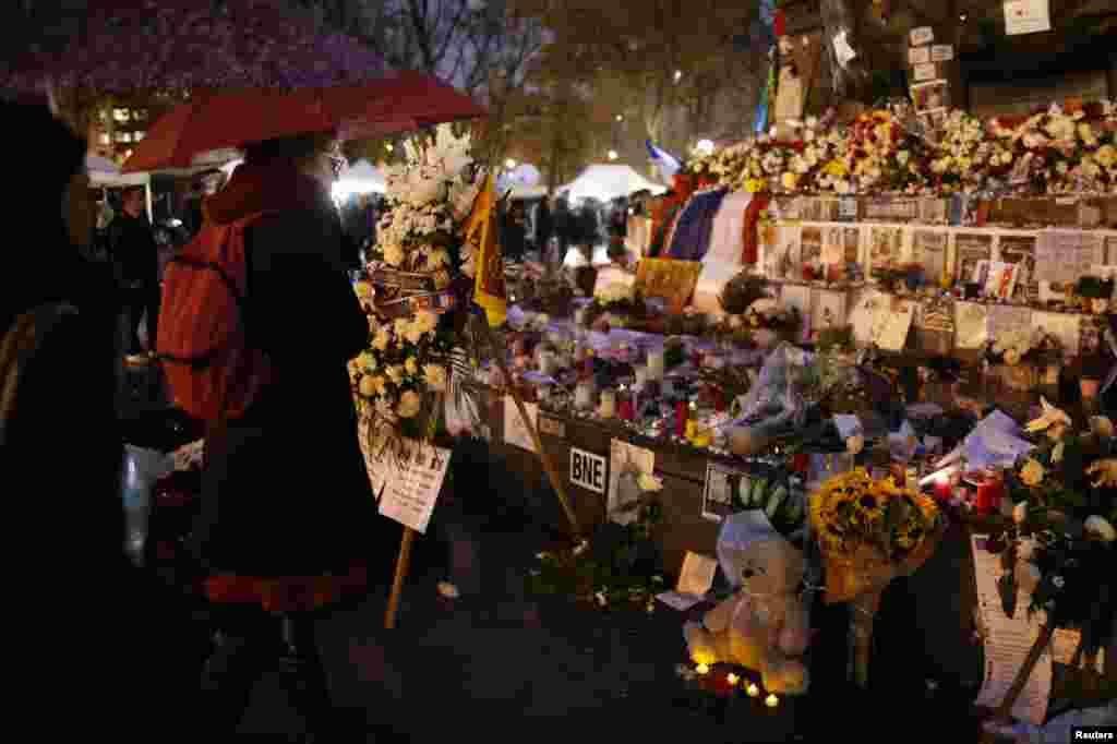 Người dân lặng nhìn hoa, nến và những thông điệp tưởng nhớ các nạn nhân tại Quảng trường Cộng hòa ở Paris, một tuần sau một loạt những vụ tấn công chết người ở thủ đô nước Pháp.