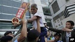 Wani dan fafatikar tabbatar da dimokaradiyya kenan ke rike da hoton dan fafatikan China dinnan da aka daure, Liu Xiaobo ya na kokarin tsallake shingen da 'yan sanda su ka gindaya lokacin zanga-zanga a ofishin jakadancin China Hong Kong