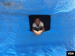 A displaced Sunni teenager looks out of a window cut into plastic blue sheeting covering his new home in the Baharka camp on the outskirts of Irbil, in the Kurdistan region of Iraq, Aug 5, 2015. (VOA / S.Behn)