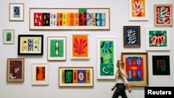 FILE - An employee poses with Henri Matisse's artworks at the Tate Modern Gallery in London, April 14, 2014.