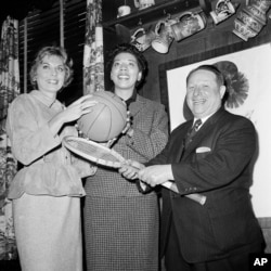 Tennis stars Althea Gibson, center, and Karol Fagerol are shown with Harlem Globetrotters' owner Abe Saperstein, where the women signed a professional contract with the Globetrotters to play at exhibition matches, Oct. 19, 1959 in New York.
