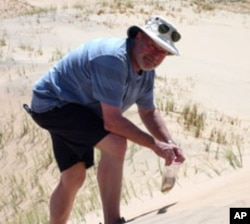 Geologist Michael Welland collects sand samples in central California.