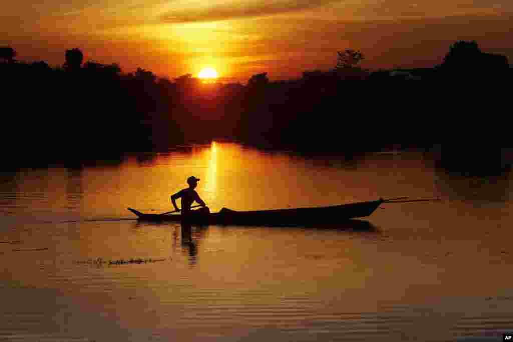 Seorang nelayan mendayung perahunya di sebuah danau saat matahari terbenam di Naypyitaw, Myanmar.