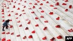 Фото: дівчинка покладає квіти до інсталяції, що засуджує насильство проти жінок, Албанія, 8 березня 2021 року