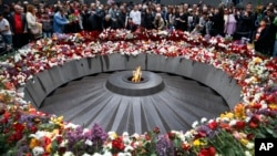 FILE - People lay flowers at a memorial to Armenians killed by the Ottoman Turks, as they mark the centenary of the mass killings, in Yerevan, Armenia, April 24, 2015.