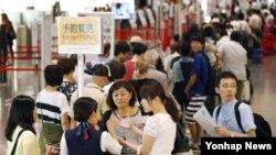 9호 태풍 민들레의 영향을 받고있는 일본 도쿄 하네다공항에서 결항이 이어지면서 승객들이 환불을 위해 줄지어 서 있다.