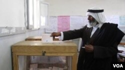 Seorang warga Mesir memasukkan surat suaranya ke kotak di TPS El-Sheikh Zouied, Sinai utara (3/1).