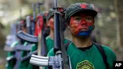 FILE - Мembers of the New People's Army communist rebels, with their face painted to conceal their identities, march with their firearms at their encampment in the Sierra Madre mountains southeast of Manila, Philippines, Nov. 23, 2016.