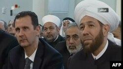 Presiden Suriah Bashar al-Assad (kiri) bersama Mufti Besar Suriah, Ahmed Hassun menghadiri peringatan Maulid Nabi Muhammad di masjid Al-Afram, Damaskus (24/1).