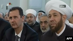 An image grab taken from the state-run Syrian TV shows Syria's embattled President Bashar al-Assad (L) siting next to Grand Mufti Ahmed Hassun during a prayer to mark the birth of Islam's Prophet Mohammed in Damascus, January 24, 2013.