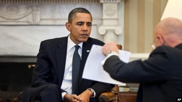 President Barack Obama studies a document held by Director of National Intelligence James Clapper during the Presidential Daily Briefing in the Oval Office, February 3, 2011.