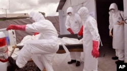FILE - health workers wearing Ebola protective gear remove the body of a man they suspect died from the Ebola virus, at a USAID, American aid Ebola treatment center on the outskirts of Monrovia, Liberia, Nov. 28, 2014.