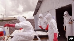 FILE - Health workers wearing protective gear remove the body of a man they suspect died from the Ebola virus at a treatment center on the outskirts of Monrovia, Liberia, Nov. 28, 2014.