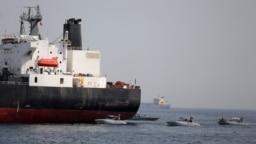 FILE - UAE Navy boats are seen next to Al Marzoqah, Saudi Arabian tanker, off the Port of Fujairah, UAE, May 13, 2019.