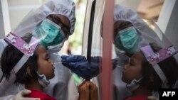 Seorang petugas medis melakukan test swab COVID-terhadap seorang anak di Surabaya (foto: AFP). RRI menutup siaran di Zona Merah termasuk RRI Surabaya.