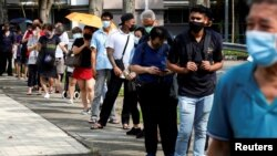 People queue up outside a quick test centre to take their coronavirus disease (COVID-19) antigen rapid tests, in Singapore September 21, 2021.