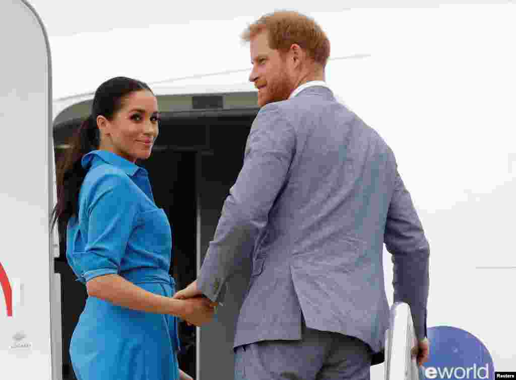 Britain's Prince Harry and Meghan, Duchess of Sussex look on before departing from Fua'amotu International Airport in Tonga.