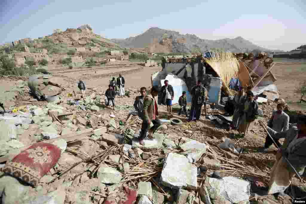 People gather around the wreckage of a house destroyed by an airstrike that killed three women and three children from one family, in the Bait Rejal village, west Sana'a, April 7, 2015.