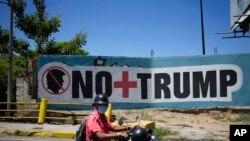 "Seorang pria mengenakan masker untuk mencegah penularan virus corona melewati mural dengan tulisan dalam bahasa Spanyol ""Tidak ada lagi Trump"" di Caracas, Venezuela, 27 Maret 2020."