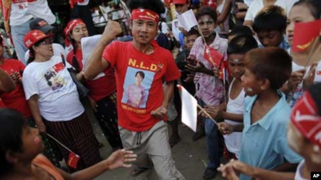 A man wearing a T-shirt bearing the image of Aung San Suu Kyi dances at campaign rally for the pro-democracy icon and her National League for Democracy, Rangoon, Burma, March 30, 2012.