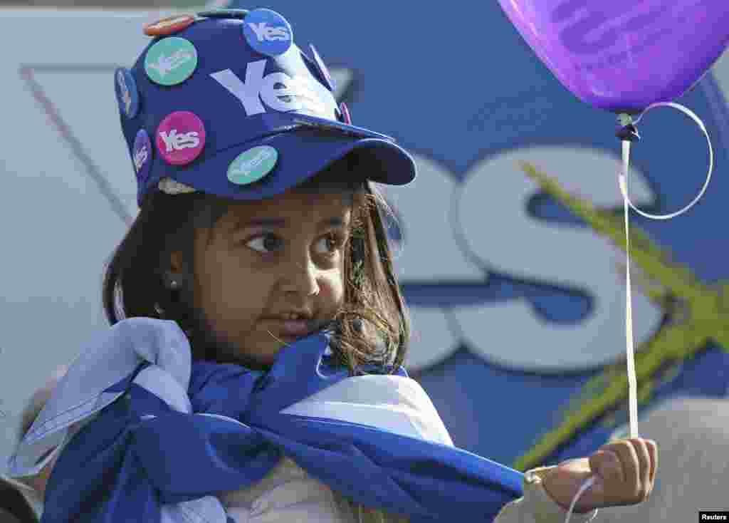 Một em nhỏ đội nón gắn những huy hiệu có chữ 'Yes' lắng nghe Thủ hiến xứ Scotland Alex Salmond vận động cho cuộc trưng cầu dân ý về sự độc lập của Scotland khỏi Vương quốc Anh ở Edinburgh, Scotland.