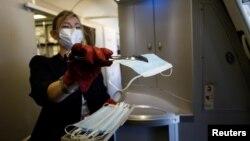 Stjuardesa francuske aviokompanije Er Frans deli maske putnicima na ulasku u avion