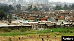Children play on the way home after school in Pumwani slums near Kenya's capital Nairobi, seen in the background, September 14, 2006.