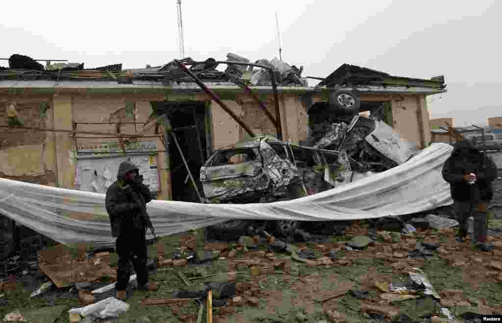 A security officer stands at the site of a blast in Kabul, Afghanistan, December 17, 2012.