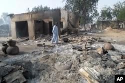FILE - A man walks past burnt out houses following an attack by Boko Haram in Dalori village near Maiduguri, Nigeria.