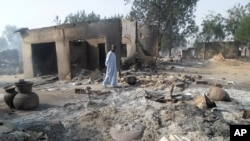 FILE - A man walks past burnt out houses following an attack by Boko Haram in Dalori village near Maiduguri, Nigeria. Abubakar Shekau says he still leads Boko Haram, exposing the biggest rift yet among Nigeria's Islamic insurgents and possibly paving the
