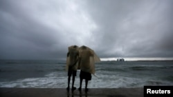 FILE - Two men use a plastic sheet to protect themselves from heavy monsoon rain as they stand by the sea in Colombo, Sri Lanka, May 17, 2018.