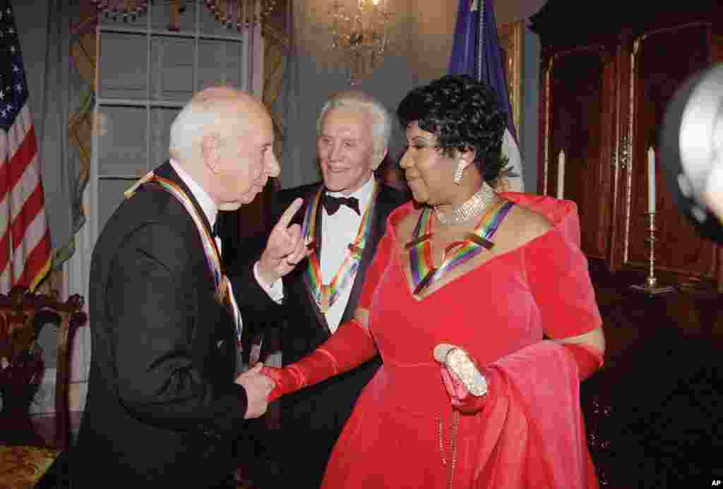 Singer Aretha Franklin listens to composer Morton Gould, as actor Kirk Douglas looks on following a dinner at the State Department in Washington, Dec. 3, 1994.