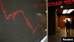 A man walks inside Athens stock exchange as a monitor shows the general index January 28, 2015. The overall Athens stock market fell almost 8 percent, while Greek five-year government bond yields hit around 13.5 percent. This marked their highest level si