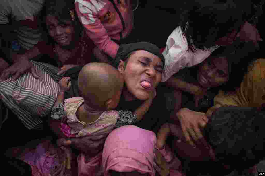 Rohingya Muslim refugees react as police and officials try to control a crowd as they wait to be called to receive food aid of rice, water, and cooking oil in a relief center at the Kutupalong refugee camp in Cox's Bazar, Bangladesh.