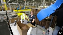 FILE - A worker places an item in a box for shipment, at a Amazon.com fulfillment center in DuPont, Washington.