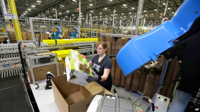 In this Feb. 13, 2015 file photo, a worker places an item in a box for shipment,at a Amazon.com fulfillment center in DuPont, Washington.
