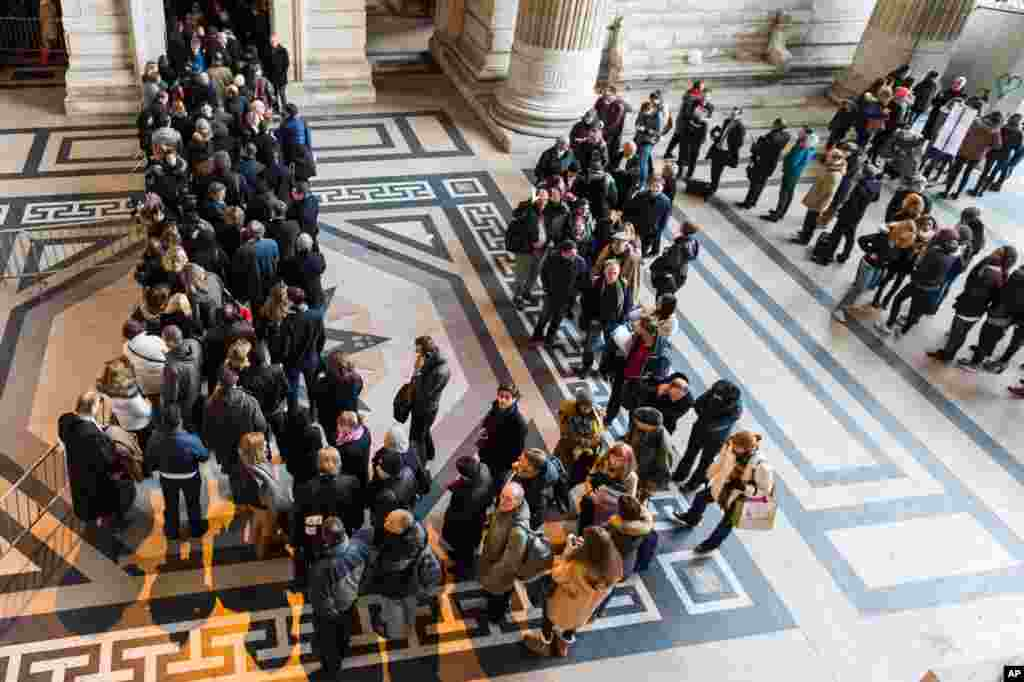 People queue as police establish a checkpoint for anyone entering the Palace of Justice in Brussels, Belgium, Jan. 16, 2015.