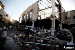People stand at the site of an airstrike on a hall where a wake for the father of Jalal al-Ruweishan, interior minister in the Houthi-dominated Yemeni government, was being held, in Sana'a, Yemen, Oct. 8, 2016.