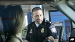 美國海關和邊境保護局一位官員在詢問一名從加拿大開車進入美國的人。
