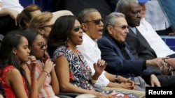 U.S. President Barack Obama and his family react along with Cuban President Raul Castro to an exhibition baseball game in Cuba.