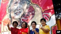 Members of Myanmar opposition National League for Democracy party pose for photos in front of a graffiti art depicting party leader Aung San Suu Kyi created by artist Arker Kyaw outside the party's headquarters in Yangon, Myanmar, Nov 13, 2015.