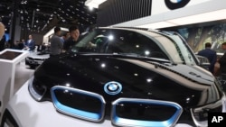 FILE - In this Wednesday, April 17, 2019 file photo, a worker cleans an electric vehicle at the BMW booth during the Auto Shanghai 2019 show in Shanghai.